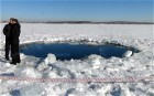 People stand near a six-metre (20-foot) hole in the ice of a frozen lake, reportedly the site of the meteor fall, outside the town of Chebakul in the Chelyabinsk region