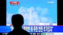 Menschen in aller Welt sehen die Explosion im Fernsehen.