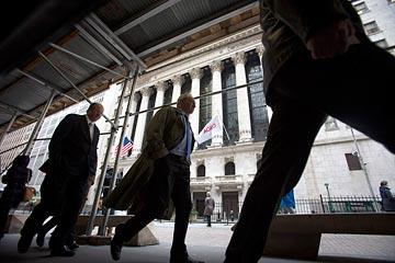 Pedestrians hasten past the New York Stock Exchange