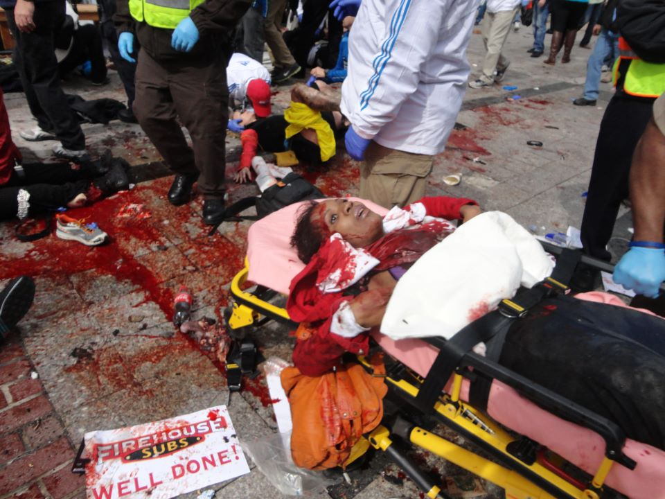 Boston Marathon black woman victim safely strapped into a gurney lying down while victim with both legs blown off is transported absurdly in a wheelchair sitting upright, unstrapped. Image via Liveleak.com