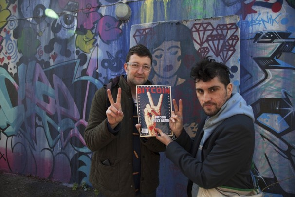 Amir Taaki and Jonathan James Harrison hold a copy of Bitcoin magazine outside the squat where subjects working with Bitcoin operate and live, in Waterloo, London.