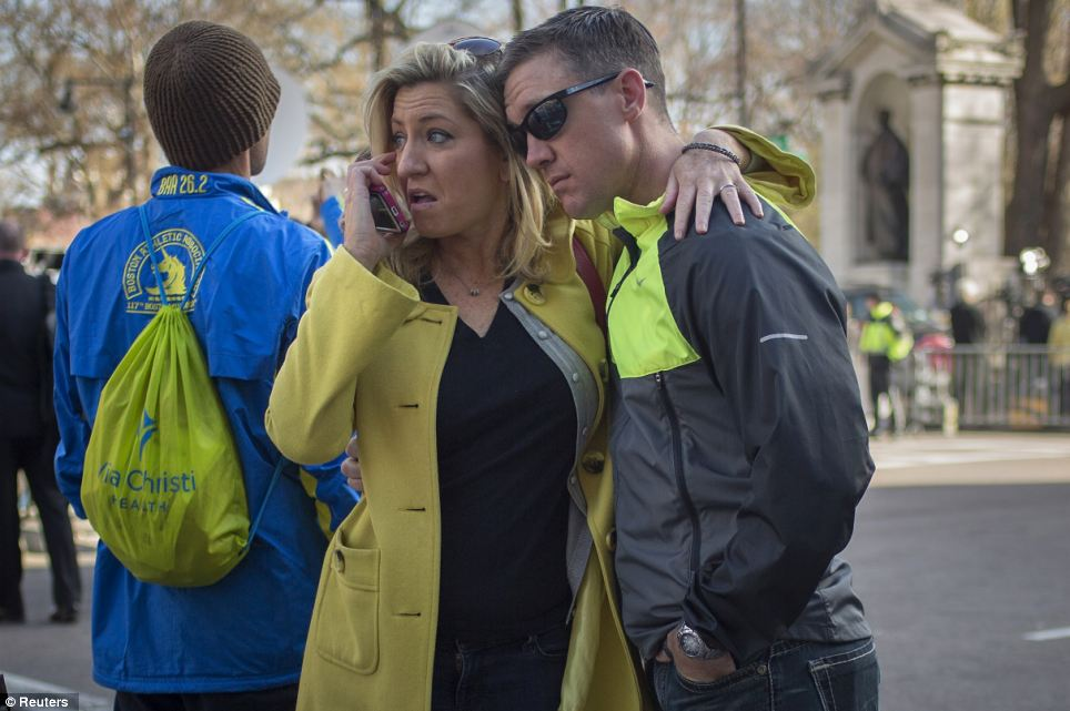 Paying respects: People embrace at Boylston Street near the finish line of the marathon on Tuesday morning, a day after the twin blasts