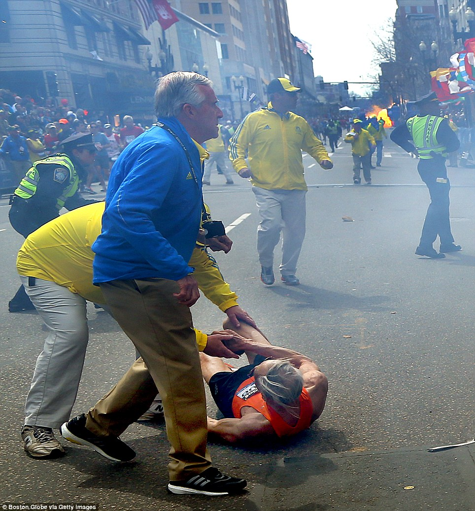 Seventy-eight-year-old Bill Iffrig, of Lake Stevens - is helped from the floor as stewards run to help those affected by the blast - as the second explosion can be seen detonating in the distance