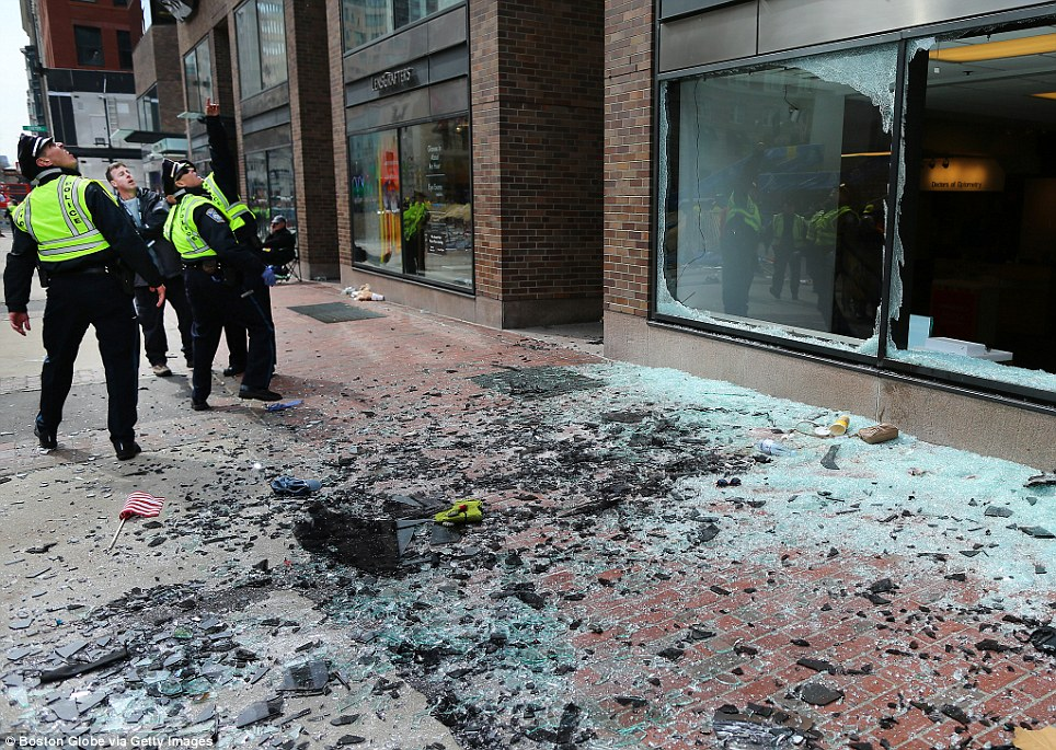 Boston police examine the damage following the massive twin detonations on Monday at the Boston marathon