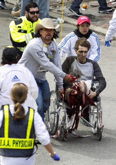 Boston Marathon victim both legs blown off sitting upright in wheelchair with loose make-belief tourniquet held by rescuer Carlos Arredondo with his hat on.