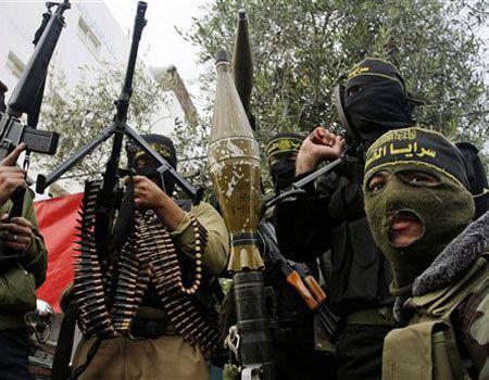 Dec. 26: Masked Palestinian militants hold their weapons during an Islamic Jihad rally in Bureij, central Gaza Strip.