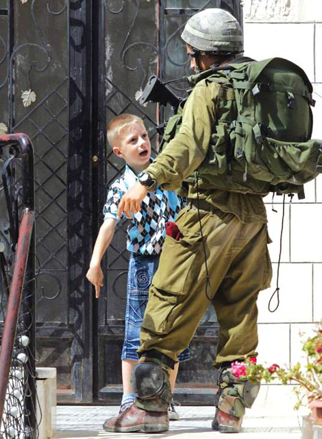 Palestinian boy guarding his house in Kyriat Arba'a Hebron photo AFP via Kawther Salam