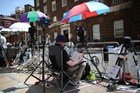 A member of the media waits outside St Mary's Hospital (Reuters)