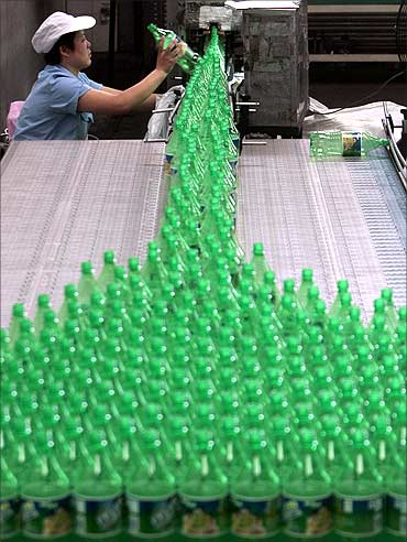 An employee works at a Sprite production line at the Coca Cola plant in Nanjing, Jiangsu province.