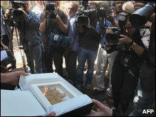 Photographers take pictures of a suspected 2,000-year-old papyrus document found by Israeli authorities in Jerusalem