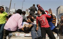 Protesters who support ousted Egyptian President Mohammed Morsi transport injured people during clashes at Ramses Square in Cairo