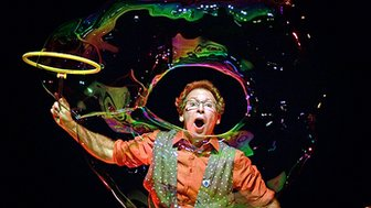Louis Pearl, a performer, blows bubbles