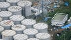 """An aerial view shows workers wearing protective suits and masks working atop contaminated water storage tanks at Tokyo Electric Power Co. (TEPCO)""""s tsunami-crippled Fukushima Daiichi nuclear power plant in Fukushima, in this photo taken by Kyodo August 20, 2013."""