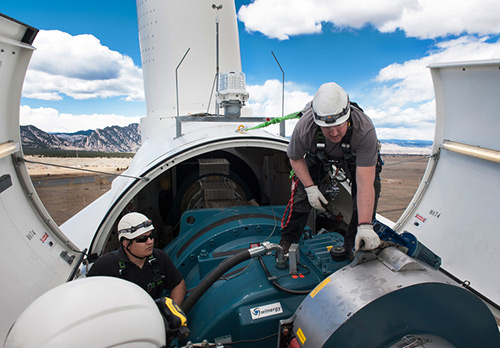 Two men work on the nacelle of a wind turbine.