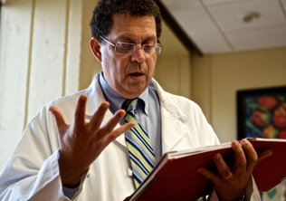 Steven Lipshultz, a pediatric cadiologist, reads medical information on Ali Scarborough, 32, of Washington, D.C., before an examination and patient consultation at the University of Miami's Miller School of Medicine in 2012. Lipshultz attended a government medical conference this week that lacked government researchers, thanks to  the federal shutdown.