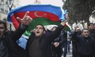 Protesters wave national flags as they rally in Baku, Azerbaijan ahead of the national elections