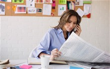 Woman reading a newspaper on the telephone