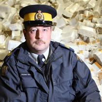 RCMP Sgt. Michael Harvey, with seized contraband cigarettes at an RCMP impound facility in Cornwall, says Cornwall-area Mounties have seized hundreds of cars, trucks, boats and trailers over the past year, along with more than 253,000 cartons of cigarettes and almost 27,150 kilograms of fine-cut tobacco.