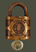 """An historical picture of an old Forest Service lock and key. The words """"Forest Service"""" and """"US"""" are engraved on the lock, with a engraved pine tree separating the """"U"""" and """"S"""". A small key is also inserted in the bottom of the lock."""