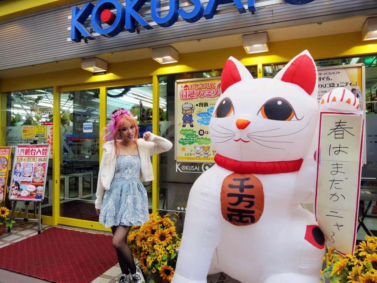 "An inflatable ""maneki neko"" stands in front of a pachinko gambling parlor, left paw raised to bring windfall."