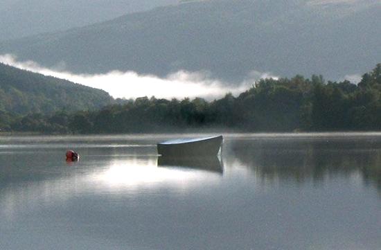 A boat sits on a still Loch at dawn