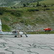 Some local pilots push their Cessna into the hangar at Courchevel airport, while firemen stand guard at the crashed Cirrus 22 in the background
