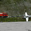 The stricken Cirrus 22 on the far end of the platform hit the mountainside. The aircraft is entangled in the blue nylon wires surrounding the field. The passenger's luggage can be seen on the tarmac, below the fire truck.