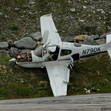 The US registered Cirrus 22 perched upon the mountain side, landing gear torn off, prop bent and for sure with more damage than is visible.The flaps are down, so the accident probably happened upon landing.
