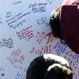 Fans write remembrances at the scene of a fiery crash that killed