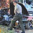 A police officer walks past the car where actor Paul Walker was killed along with another unidentified man during a car crash in Valencia