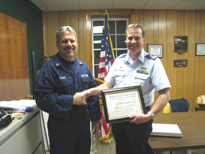 Auxiliarist George Tranos receives award from Flotilla Commander John Dibbons