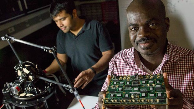 Kwabena Boahen, right, holding a biologically inspired processor attached to a robotic arm, with student Samir Menon in a Stanford University laboratory.