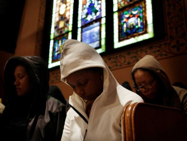Congregants bow their heads in prayer during a service at Middle Collegiate Church in New York, Sunday, March 25, 2012. Church-goers were invited to wear hoodies to services to show their support for justice in the case of Trayvon Martin, an unarmed black teenager who was wearing a hoodie on the night he was killed by a neighborhood watch captain in Florida. (AP Photo/Seth Wenig) Photo: Seth Wenig