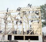 a large group of men building a barn