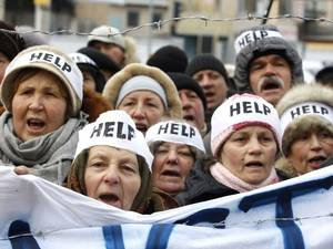 Protesters wearing headbands reading 'Help' shout slogans during an action entitled 'Impose sanctions - stop the violence' in front of the European Union delegation in Ukraine in Kiev. Participants of the rally urged the European Union to immediately impose personal sanctions for those responsible for the use of force against peaceful protesters and journalists, as well as involved in the adoption of unconstitutional laws in Ukraine that violate fundamental human rights