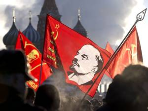 21 January 2014: Russian Communists, carrying red flags with portrait of Soviet founder Vladimir Lenin, form a long queue as they visit the Mausoleum during Lenin's 90th death anniversary at Moscow's Red Square in Russia