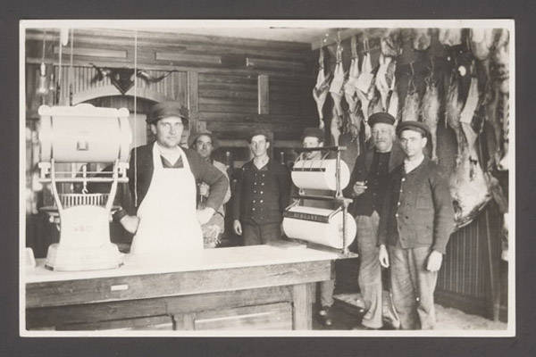 John Nelson's photograph depicts a butcher and his helpers inside a butcher shop. NSHS RG3542.PH:095-21