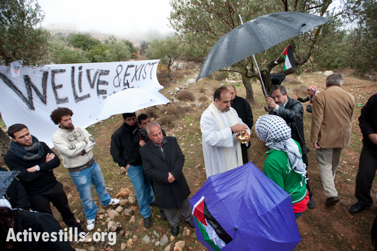 Bethlehem-area Christians joined by local and international activists gather for a Catholic mass to protest the Israeli separation wall that will cut off Beit Jala's Cremisan monastery and winery from nearby West Bank communities, November 18, 2011.