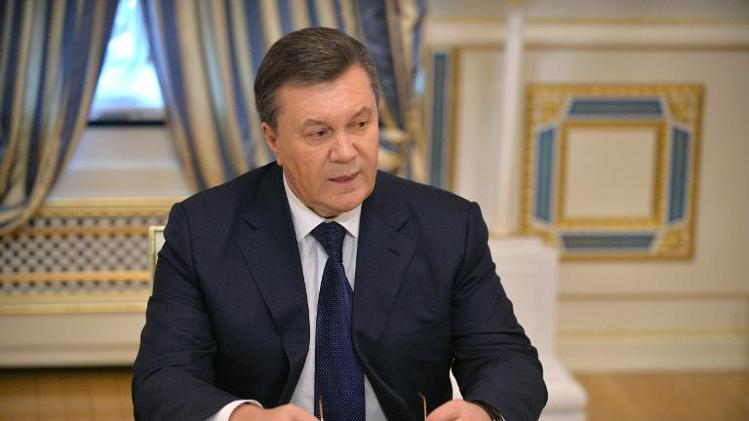 Ukrainian President Viktor Yanukovych signs an agreement in Kiev on February 21, 2014 to end the country's worst crisis since independence