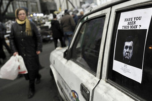 """Ukrainians look at a """"Wanted"""" notice for fugitive Ukrainian President Victor Yanukovich, plastered on the window of a car used as barricade near Kiev's Independent Square February 24, 2014. Ukrainian President Viktor Yanukovich, ousted after bloody street protests in which demonstrators were shot by police snipers, is wanted for mass murder, authorities announced on Monday. REUTERS/Yannis Behrakis"""