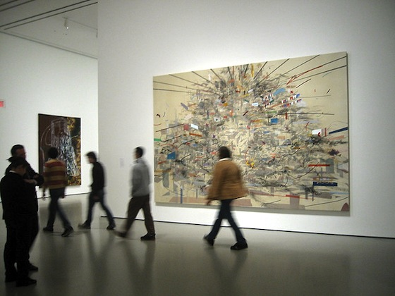 Visitors at The Museum of Modern Art in front of Julie Mehretu, Empirical Construction, Istanbul, 2003. Ink and synthetic polymer paint on canvas, 10' x 15' (304.8 x 457.2 cm).