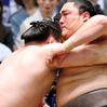 Yokozuna Hakuho, left, forces No. 2 maegashira Okinoumi out of the ring on Day 4 of the Spring Grand Sumo Tournament at Osaka's Prefectural Gymnasium on March 12. (Yoshiko Sato)