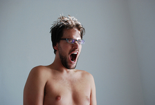 A man without a shirt yells in anger.