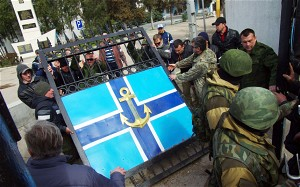 Pro-Russian protesters remove the gate of Ukrainian navy headquaters as Russian troops stand guard in Crimean city of Sevastopol