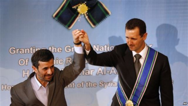Iranian President Mahmoud Ahmadinejad, left, holds up the hand of his Syrian counterpart Bashar al-Assad after he was awarded Iran's highest national medal in a ceremony in Tehran, Iran, 2 Oct 2010