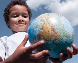 Image of a smiling boy holding a globe