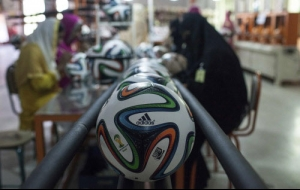 Employees work near official 2014 World Cup balls at the final stage of their quality...