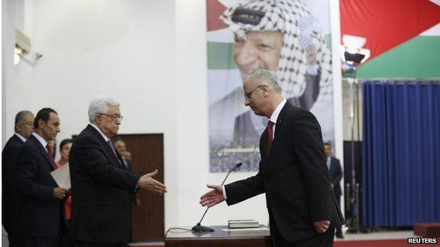 Palestinian President Mahmoud Abbas shakes hands with Rami Hamdallah at swearing-in ceremony in Ramallah (02/06/14)