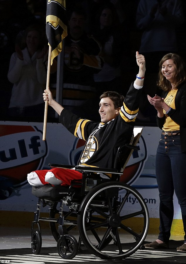 Caption (by UK Daily Mail) We will overcome: Boston Marathon bombing victim Jeff Bauman smiles as the crowd cheers for the 27-year-old at the Boston Bruins game on Saturday (Image via UK Daily Mail, 4-May, 2013, read the full article titled: Boston Strong! Bombing double amputee Jeff Bauman leaves hospital just 19 days after blast to open Bruins hockey game)