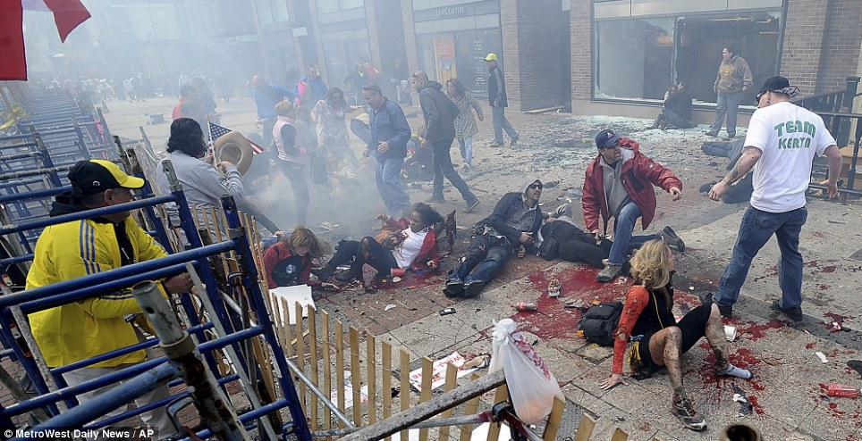 Boston Marathon victim with both legs blown off lying unattended on the ground behind the black woman while rescuer Carlos Arredondo with his hat and american flag looks on. Image via uk dailymail april 16 2013 article-2309545